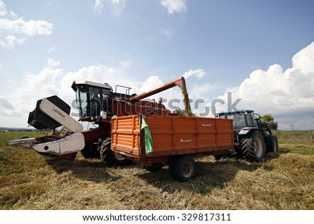 VITERBO, ITALY - 25 JULY 2014: A combine harvester transferring durum wheat to a waiting tractor and trailer after cutting a field during the summer harvest in Viterbo.