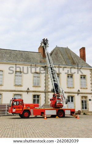 VITRE, FRANCE - JULY 12, 2014: Firemen carry out training exercise near the building at the castle square of Vitre. The castle of Vitre was built in 11th century and rebuilt at 13th century. - stock photo