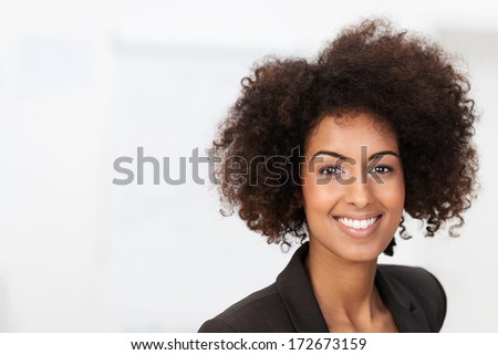 Vivacious African American businesswoman with a beaming smile and afro hairstyle looking at the camera over white with copyspace - stock photo
