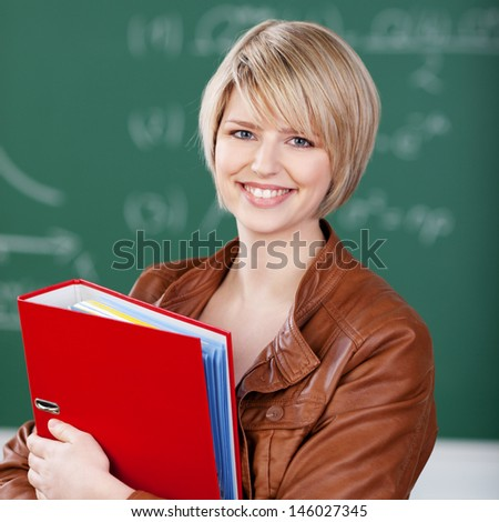 Vivacious beautiful young blond female student in a trendy leather jacket with a binder containing class notes clasped to her chest - stock photo