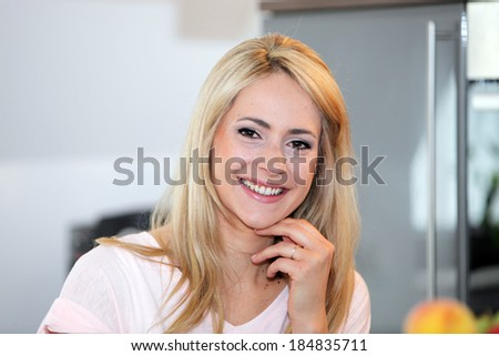 Vivacious beautiful young blond woman with a friendly smile sitting in her dining room, close up facial portrait - stock photo