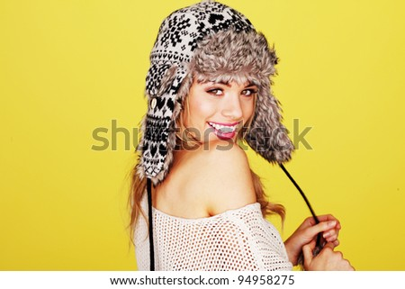 Vivacious happy young woman in a woolly winter hat with earflaps looking over her shoulder at the camera. - stock photo