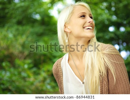Vivacious laughing young blonde model looking back over her shoulder in merriment against greenery foliage. - stock photo