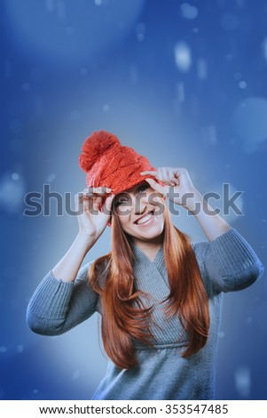 Vivacious laughing young redhead woman in a festive red hat standing outdoors in falling snow smiling merrily at the camera, copy space for a Christmas or seasonal greeting
