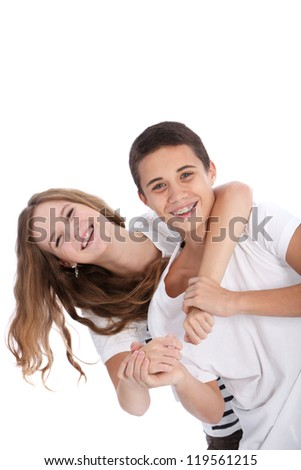 Vivacious laughing young teenage boy and girl having fun playing around together with the girls arms around the boys neck from behind isolated on white