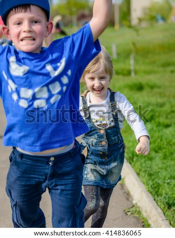 Vivacious spontaneous pretty little blond girl running and laughing along a path with her brother as they go out to play in the sunshine, fathers legs visible behind - stock photo