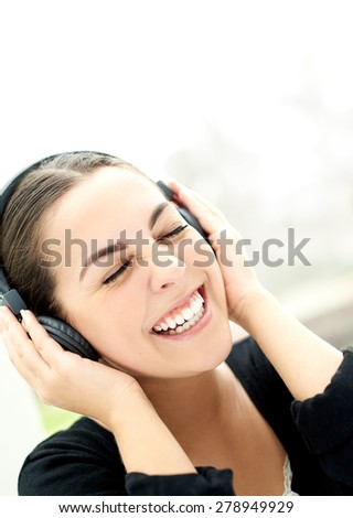 Vivacious young woman enjoying her music laughing as she holds her headphones to her ears, close up of her face with her eyes closed in bliss - stock photo