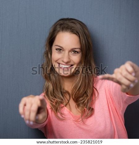 Vivacious young woman pointing at the camera with both hands, focus to her face and charming smile - stock photo