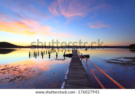 Vivid and colourful sunset and reflections at mid tide, Yattalunga Australia.   Jetty wharf and harbour pool, boats and yachts moored on waters at Yattalunga, NSW Central Coast, Australia.   - stock photo