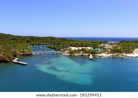 Vivid blue tropical ocean water landscape with trees and land in the background and a bright blue sunny sky. - stock photo