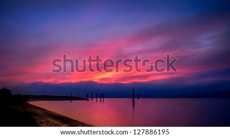 Vivid color lights up this magnificent landscape as the sunset brilliantly fills the blue sky with bright pink, yellow and purple and reflects in the smooth ocean water. - stock photo