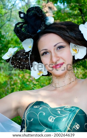 Vivid color photographs of beautiful young girl with dark hair. Forest nymph, fairy. Fairy tale, fantasy. Floristics and design, decoration. Hairstyle, reminiscent of medieval