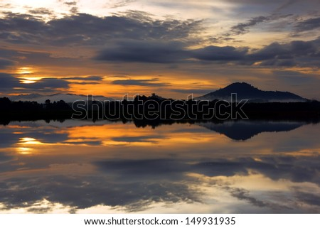 Vivid colors and reflections at dawn over lake in Thailand - stock photo