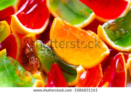 Vivid colour, red, green, orange, jelly in oranges peel. Full frame macro background in bright natural light
