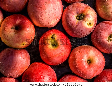 Vivid freshly picked red apples close up background with contrasting shadows - stock photo