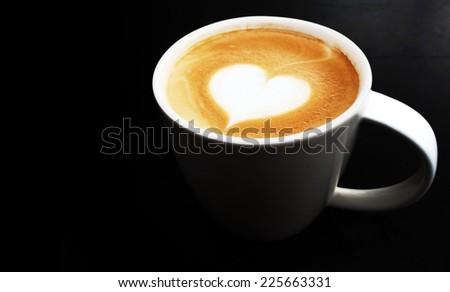 vivid lighting cup of latte art coffee  on dark background  - stock photo