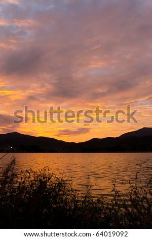 vivid orange sunrise over pond in japan - stock photo