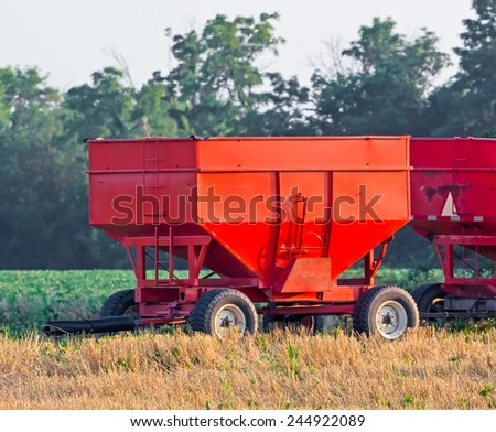 Vivid red grain wagons are parked alongside a farm soybean field at harvest time in the American Midwest. - stock photo
