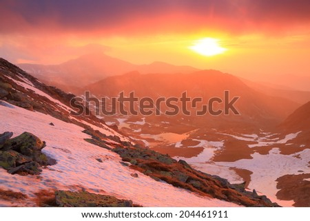 Vivid sky at sunset above snow covered mountains