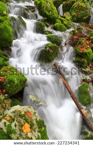 Vivid stream of water flowing over the rocks in autumn - stock photo