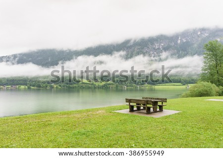 Vivid summer nature of Austria mountains, Tirol. Brown wooden bench near the lake. Tranquility of a warm rainy day in Alps, Europe. - stock photo