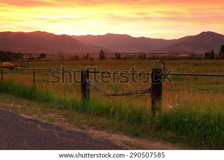 Vivid sunset above rural fields and fence posts, Utah, USA. - stock photo