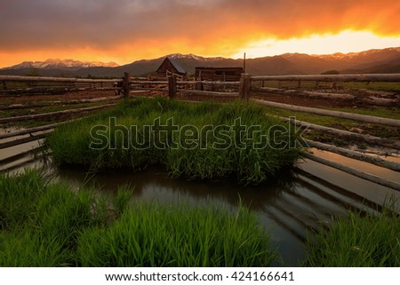 Vivid sunset with fence poles and an old barn in rural Utah, USA. - stock photo