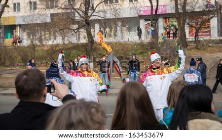 VLADIVOSTOK, RUSSIA - NOVEMBER 16: torchbearer carries the Olympic flame in relay of Olympic Flame on November 16, 2013 in Vladivostok, Russia.