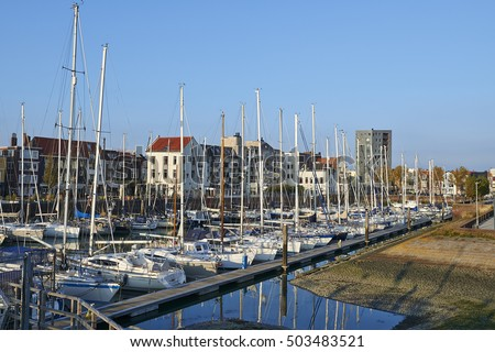 VLISSINGEN, NETHERLANDS, OCTOBER 22, 2016; Old harbor of the Dutch town of Vlissingen or Flushing, with sailing boats and old houses on the quay under a beautiful blue sky