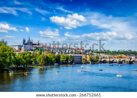 Vltava river and Gradchany (Prague Castle) and St. Vitus Cathedral and Charles bridge with people in paddle boats. Prague, Czech Republic - stock photo