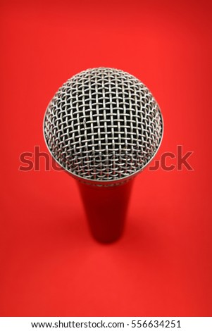 Vocal microphone high angle view close up over red background, personal perspective