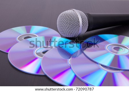 Vocal microphone on cd discs, closeup - stock photo