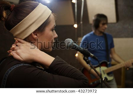 vocalist girl is singing. electrical guitar player in out of focus - stock photo