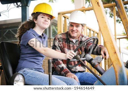 Vocational instructor teaching a young construction apprentice how to drive heavy equipment.   - stock photo