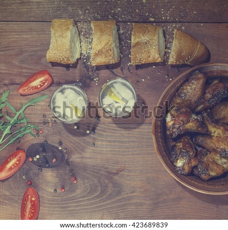 Vodka, gin, tequila. fried chicken legs and fried chicken wings , Cherry tomatoes, Spices, baguette, Italian food. Vodka, gin, tequila in a glass with ice on a wooden  - stock photo