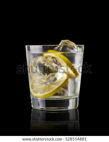Vodka lime, gimlet or gin tonic with ice in glass on black background  - stock photo