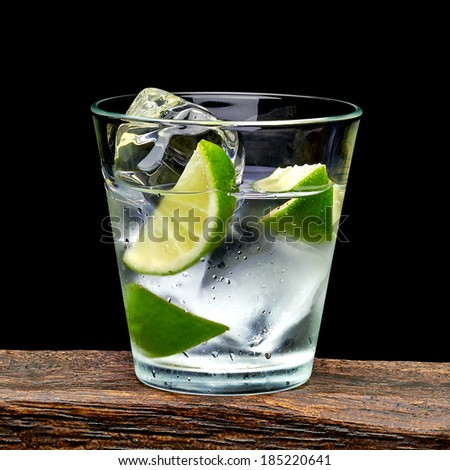 Vodka lime wedge with ice in rocks glass on log with black background  - stock photo