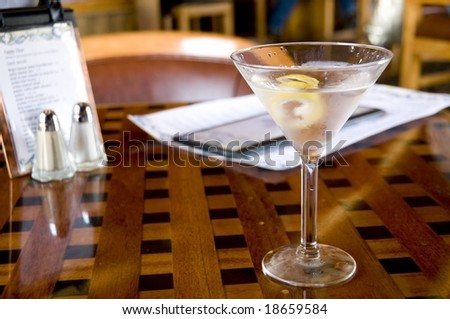 Vodka Martini with a twist on a cocktail lounge table - stock photo