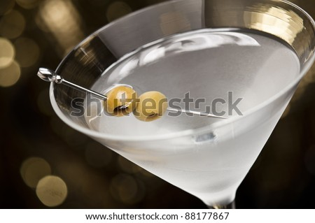 Vodka Martini with olive garnish in front of a gold glitter background - stock photo