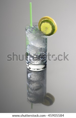 Vodka or Gin & Tonic mixed drink with lemon and lime slice garnish on grey background with reflection - stock photo