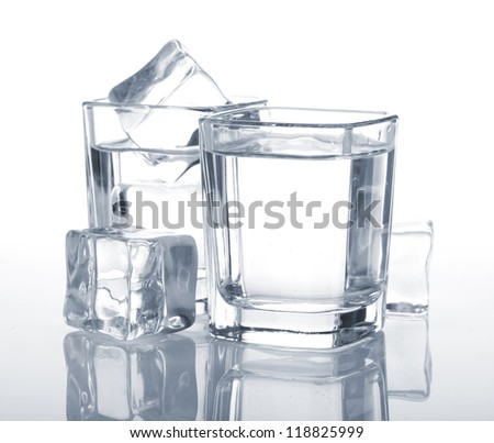 Vodka shots with ice cubes. Blue toned - stock photo