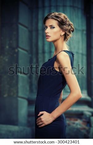 Vogue model wearing black dress posing over urban background. Fashion shot. - stock photo