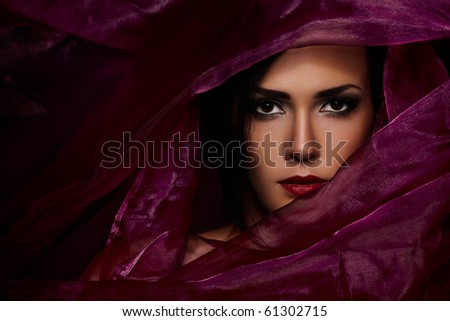Vogue portrait of a beautiful lady covered in violet fabrics