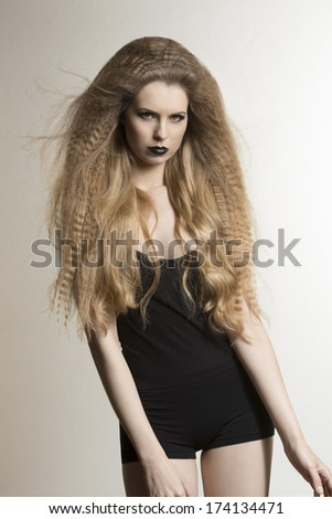 vogue portrait of fashion dark lady with long blonde flying hair-style, strong make-up and sexy black underwear