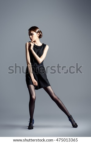 Vogue shot of a female brunette model posing at studio. Full length.