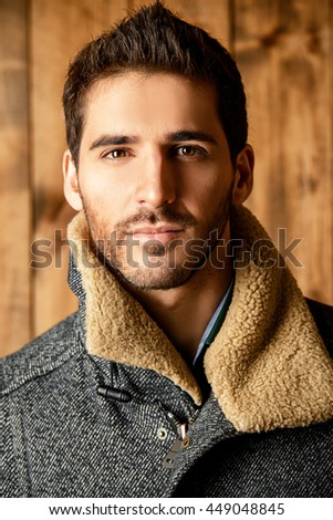 Vogue shot of a handsome male model in a coat standing by a wooden wall. Men's beauty, seasonal fashion.  - stock photo
