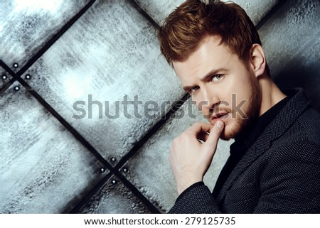 Vogue shot of a handsome man in black suit posing at studio. Men's beauty, fashion. - stock photo
