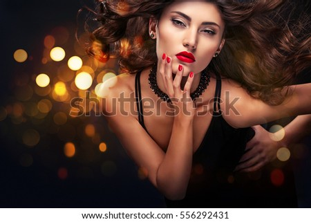 Vogue style close-up portrait of beautiful woman. Long curly brunette hair on black background with lights. St valentine's day