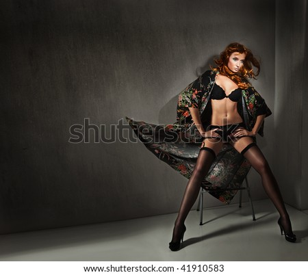 Vogue style photo of a young beauty over dark wall - stock photo