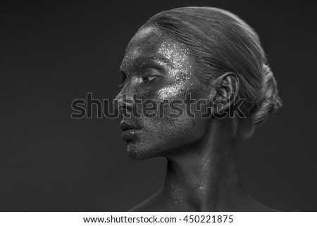 Vogue style portrait of a woman. Black makeup with glitter. Dark background. Black and white
